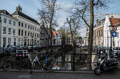 Along the Nieuwegracht (mikebakker2) Tags: utrecht stad provincie city province nederland netherlands thenetherlands holland architecture architectuur street straat downtown innercity binnenstad house houses huis huizen building buildings bridge brug bike bicycle bikes bicycles scooter moped water canal gracht tree trees boom bomen domtoren dom church kerk cathedral kathedraal toren tower perspective angle quiet peaceful quaint winter day blue sky light bright sunlight