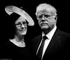The Hat (Neil. Moralee) Tags: wedding portrait bw woman white man black love monochrome face up hat fashion shirt lady contrast pose beard him mono glasses necklace high couple close married faces affection pair trimmed tie marriage neil husband her devon mature his wife elaine guest suite hers dressed fashionable whitehair middleaged whitebeard fascinator hemyock moralee neilmoralee rosskirstyneilmoralee
