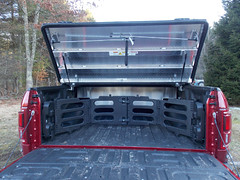 A Heavy Duty Truck Bed Cover On A Ford F150 Raptor (DiamondBack Truck Covers) Tags: aluminum tonneaucover truckbedcover diamondback diamondplate pickuptruck redtruck ruggedblack ford f150 ff15 raptor c hd heavydutytruckbedcover cb20 0015000001ig5xiaar outdoors woods rearview onepanelopen tailgatedown