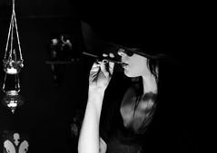 Aloof BW (skippyclese) Tags: pierced blackandwhite bw woman hat sunglasses dark blackwhite necklace cheek arm goth shades smoking hanging cleavage piercings brim