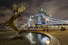 Girl with a dolphin fountain & Tower Bridge (Jaime Hernández Pérez) Tags: fountain tower bridge towerbridge london night lights city cityscape water longexposure canon80d canon1022 clouds uk fuente torre puente londres noche luces ciudad agua largaexposicion architecture arquitectura