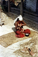 21-396 (nick dewolf photo archive) Tags: nepal houses people woman baby house color building film rural scarf 35mm buildings infant village child feeding 21 nick mother mat nepalese breastfeeding 1970s 1972 youngwoman himalayas villagers villager nepali dewolf headcovering mountainvillage ruralvillage nickdewolf photographbynickdewolf ruralnepal reel21 hillyregion