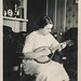 Woman plays a mandolin in her bedroom