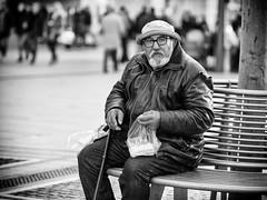 Having a snack (graveur8x) Tags: man snack candid street portrait dof blackandwhite old strange glasses frankfurt germany deutschland strase streetphotography zeil hat bread bench monochrome bw schwarzweis lumix panasonic panasonicdmcgx80 lumixgx80 olympus olympusm75mmf18 75mm microfourthirds m43 people person leatherjacket
