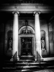 In Buildings Of Wood And Stone We Lay To Rest Flesh And Bone (Ghost Of Nations Photography And Digital Art) Tags: door blackandwhite bw sculpture cemeteries black church cemetery graveyard statue gloomy entrance churches creepy column saintjoseph mortuary ghostofnations ghostofnationsphotography