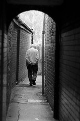 Through the Alley (Just Ard) Tags: street uk urban bw white man black monochrome wall wales walking photography prime mono alley nikon candid cymru streetphotography 85mm lane monmouth nikkor unposed brisks primelens d7000 justard