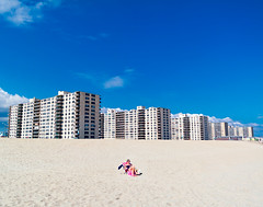Rockaway Beach (Gimo Nasiff) Tags: new york sky woman sun beach 30 lady clouds america buildings lens person sand united tan samsung shades queens kit states leaning tanning rockaway nx 1850mm gimo nx30 nasiff ditchthedslr