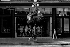 Passer By (douglasdrouin11) Tags: street city light people urban blackandwhite bw stilllife canada man lamp car vancouver contrast truck 35mm person photography 50mm town day cityscape bc chairs britishcolumbia mainland urbanscape