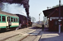 'Awaiting the Off' (2)  |  Rakoniewice, PKP  |  2006 by keithwilde152 - A Springtime scene at Rakoniewice; the lady stationmaster appears from inside near to departure to wave-off the 11.36 Wolsztyn-Poznan Gl passenger headed by Ol49 23. 21st April 2006