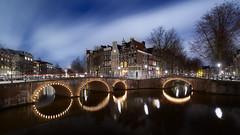 De essentie van Amsterdam (zsnajorrah) Tags: urban bridge canal water reflection trees streetlight lantern sky clouds motion evening night bluehour twilight longexposure 7dmarkii efs1018mm netherlands amsterdam keizersgracht leidsegracht