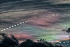 A plane flies 'through' iridescent clouds