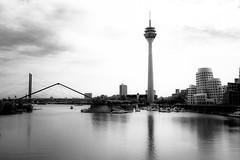 Rheinturm (Alex Schraufstetter Photographer) Tags: bridge sky bw clouds 35mm nikon cityscape dramatic dsseldorf rheinturm medienhafen gehrybauten d700
