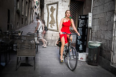The Woman in Red (Miklos Szaloczy) Tags: street red italy bicycle lumix restaurant europe dress stones candid olympus riding 17 pancake 20mm 20 narrow omd 2014 1720 em5