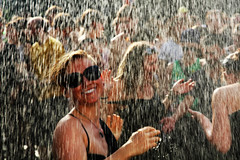 Dancing in the Rain (Jungle C) Tags: world carnival summer woman berlin wet water girl sunglasses rain smiling festival topv2222 lite fire faces bokeh artificial topv5555 heat tropical topv3333 topv4444 cultures brigade refreshment natgeo 3000v120f elitephotography natgeofacesoftheworld