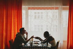 Breakfast together (Yuliya Bahr) Tags: red woman man black berlin love window smile silhouette breakfast germany table happy engagement hands african couples lifestyle international together laughter internationallove hochzeitsfotografberlin  hochzeitsfotografkln hochzeitsfotografdresden hochzeitsfotografharz hochzeitsfotografmnsterhochzeitsfotografrostockhochzeitsfotografulm          familienfotogafberlin familienfotografhamburg familienfotogafberlin