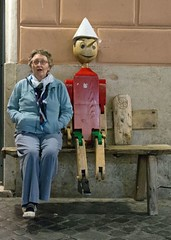 Seated with Pinocchio (john atte kiln) Tags: seated pinocchio seat surprised woman puppet model rome roma italy lazio carlocollodi nose lying wood wooden icon blue bluejacket bluetrousers blocks machined missingfoot marionette lifesize bench wall tiles