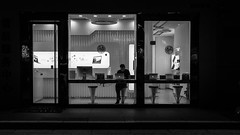 Overtime (Go-tea 郭天) Tags: qingdaoshi shandongsheng chine cn qingdao huangdao shop windows night staff work working worker seller saler computers apple light dark seated seat laptop desktop bar chairs high duty busy job business commercial street urban city outside outdoor people bw bnw black white blackwhite blackandwhite monochrome asia asian china chinese shandong canon eos 100d 24mm prime indoor inside man young technology hitech open mac