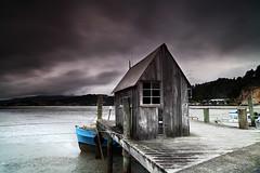 The Gay Dolphin Coromandel (angus clyne) Tags: boat pier long exposure coromandel new zealand sea bay mud blue shed hut dawn grey dark storm gay dolphin fishing mussel town village nz north island coast