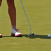 Golfer rolls a ball towards the cup during time on the practice green at Pinehurst No. 2.
