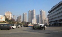 "North Korea P'yongyang streetview with view of 'Dubai Section' towers going up (2011) - ""Construction Time Again"" (moreska) Tags: architecture construction asia apartments jeep empty towers north murals korea vehicles plazas asphalt development streetview trolleybus pyongyang dprk 2011 parkingarea socialiststructures"