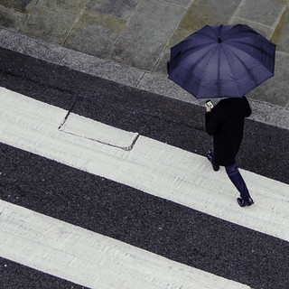 Man Crossing Road with Umbrella