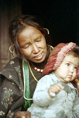 21-289 (ndpa / s. lundeen, archivist) Tags: nepal people woman baby mountain color film girl face rural 35mm necklace beads infant village child faces 21 nick jewelry earrings nepalese 1970s 1972 himalayas villagers villager nepali dewolf piercednose mountainvillage ruralvillage nickdewolf localwoman photographbynickdewolf ruralnepal reel21 hillyregion