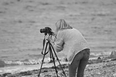 "Doing The Biz (steiner2009 ""AKA Dr Dust "") Tags: camera sea blackandwhite woman beach female sand waves photographer coat tripod norfolk pebbles candidshot candidphotography"