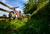 Crotch rocket (Stickyemu) Tags: blue red green grass bike fence landscape suffolk nikon outdoor mtb 2009 hff specializedrockhopper 18105mm mountingbike nikond7100