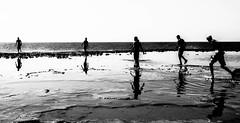 Walking shadows (Houssam Alami) Tags: bw playing reflection beach water blackwhite waves shadows reflect strength