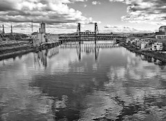 the castled clouds  mocked themselves (1crzqbn) Tags: bw sunlight clouds reflections cityscape textures pdx willametteriver hss thesteelbridge 1crzqbn theoregonconventioncenter thecastledcloudsmockedthemselves