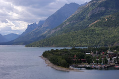 Waterton, AB (Justin van Damme) Tags: blue trees people lake canada mountains green beach water clouds landscape rockies boats town site dock haze ab alberta tiny waterton