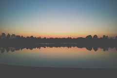 calm (itawtitaw) Tags: trees light sunset sun lake color reflection water contrast mirror evening dusk low samsung tranquility bluesky calm shore mobilephone divided sgs2