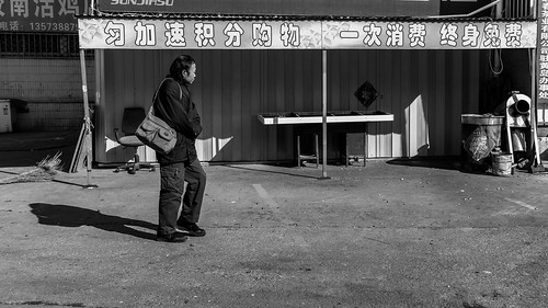man old bag alone lonely loneliness walk walking movement sun shadow cold winter construction site characters dirty zone area clean dust through street urban city outside outdoor people bw bnw black white blackwhite blackandwhite monochrome asia asian china chinese shandong canon eos 100d 24mm prime straight forward direction qingdao huangdao portrait candid candide