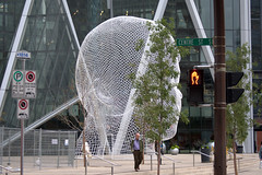the head of Calgary, AB (Justin van Damme) Tags: street trees light sculpture canada man calgary giant walking wire mesh head centre ab alberta bow daytime wonderland