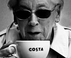 Trimethylxanthine. (Neil. Moralee) Tags: old portrait blackandwhite bw woman costa white black hot cup coffee monochrome face dark glasses big nikon energy close cola tea sleep coat beverage drinking neil tolerance mature collar caffeine insomnia wrinkles gulp sip swig caffeinated dependance psychoactive moralee monochromtic trimethylxanthine aw110