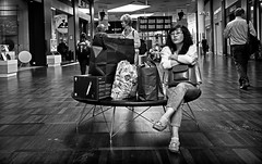Taxfree Shopping Extravaganza (Anne Worner) Tags: street woman copenhagen denmark airport sitting candid seat streetphotography ricohgr kastrup shoppingbags anneworner