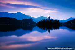 Sunrise at Lake Bled (Ian Middleton: Photography) Tags: morning travel vacation cloud lake holiday mountains alps building tower history tourism church nature water beautiful architecture sunrise religious island boat scenery europe european bell famous mary scenic eu architectural historic christian hills spire touristy stunning bled backdrop former christianity popular yugoslavia assumption attraction slovenian slovene gorenjska slavic karavanke mountstol