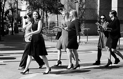 Sales Meeting (burnt dirt) Tags: houston texas downtown mainstreet street sidewalk streetphotography fujifilm xt1 girl woman people person city town heels glasses sunglasses purse bag leftovers doggiebag building office restaurant asian group crowd walking talking blonde longhair curls ponytail bw blackandwhite