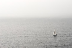 lonely sailboat on water (Mimadeo) Tags: ocean seascape water fog sailboat marina landscape outdoors one freedom boat marine solitude alone sailing ship peace view yacht lifestyle overcast aerial adventure maritime sail lonely solitary distant yachting navigating