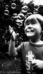 Grabbing some bubble time. (broadswordcallingdannyboy) Tags: bubbles bubblebursting fun play joy playtime childrenplaying eos7d 1740mm childrenplayingwithbubbles ageofinnocence childrenbeingchildren bw bwchild bwportrait bwboy boy portrait canon llens naturallight leonreillyphotography blackandwhiteportrait bwchildportrait leonreilly canoneos