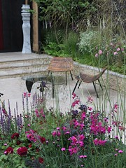 Seating area behind the flowers in a show garden (Carol Spurway) Tags: show pink flowers flower london glass stone table chelsea chairs pillar steps column rhs 2014 chelseaflowershow showgarden