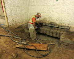 A worker removes slab and foundation to prepare duct routing. The highest priority for the Capitol Restoration Project is to update the infrastructure supporting the Capitol. (Photo courtesy JE Dunn Construction) (Minnesota State Capitol Restoration Project) Tags: people minnesota stone architecture construction state interior basement stpaul foundation dirt capitol infrastructure restoration worker mn statecapitol historicpreservation hardhats 1905 mep 2014 historicbuilding