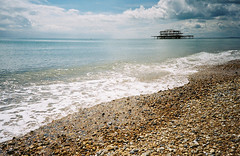 LC-A+ - West Pier From The Beach (johnnytakespictures) Tags: ocean blue sea summer sky sun holiday film beach sunshine clouds fire sussex seaside lomo lca lomography ruins brighton tide pebbles front lomolca damage analogue seafront damaged derelict arson dereliction pebbly ruined cn100 lomographycn100