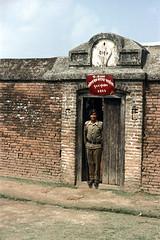 21-033 (ndpa / s. lundeen, archivist) Tags: door nepal people man color building film 35mm uniform 21 nick guard doorway nepalese 1970s beret 1972 himalayas brickbuilding nepali dewolf uniformed 2029 guardpost nickdewolf photographbynickdewolf reel21 hillyregion