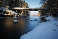 Let the sun light the scene. (laurilehtophotography) Tags: konnekoski konnevesi suomi finland nikon d3100 nature stream trees forest bridge road snow ice water longexposure sky landscape koski silta metsä tie talvi winter winterwonderland nikkor 1755mm f28g