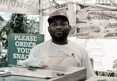 The Street Snack Vendor [Explored] (The_Kevster) Tags: street leica light portrait sky food signs man london clouds person focus shadows bokeh stall rangefinder leytonstone worker vendor caribbean seller eastlondon summicron50mm leicam9