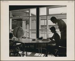 A man and woman at a table reading a book at the Kitimat Public Library, Kitimat, British Columbia / Un homme et une femme assis à une table lisent un livre à la Bibliothèque Kitimat (Colombie-Britannique)