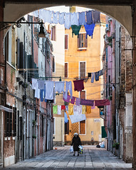 Walking Under Laundry (Trouvaille Blue) Tags: europe italy italia venice venezia calle laundry woman shopping trouvailleblue