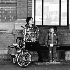 Waiting for the train to come (Akbar Simonse) Tags: bw woman holland blancoynegro netherlands monochrome station bicycle bench kid child zwartwit ns nederland streetphotography bank denhaag bn kind thehague vrouw fiets foldingbicycle hollandspoor lahaye sgravenhage vouwfiets agga straatfotografie akbarsimonse