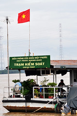 Just don't barge in... (Roving I) Tags: vertical boats flags vietnam rivers shipping saigon hcmc aerials hochiminh barges borderguards checkpoints